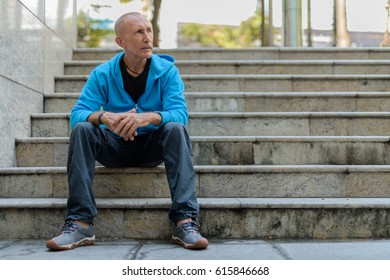 Full body shot of bald senior man thinking while sitting on the staircase in Bangkok Thailand
