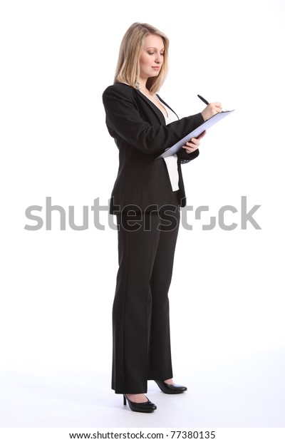 Full body shot of a beautiful blonde business woman writing and taking notes on a clipboard. She is wearing a smart black business suit and high heels.