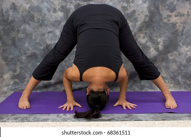 Full body shot of caucasian brunette woman against a mottled background on purple yoga mat doing a wide legged forward fold bend yoga pose.