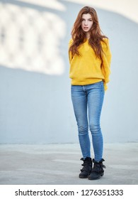 Full body shot of fabulous redhead woman with long hair in yellow sweater having fun on grey concrete wall background with sun light spots.