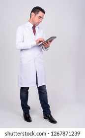 Full body shot of handsome man doctor with protective glasses using digital tablet