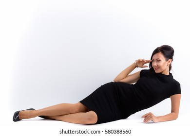 Full body shot of happy beautiful businesswoman smiling and lying down while thinking