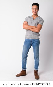 Full body shot of happy Hispanic man smiling with arms crossed