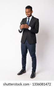 Full body shot of happy young handsome African businessman using phone