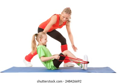 Full body shot of a little girl doing exercise with weights with an instructor on the mat. Orange, green and black colors