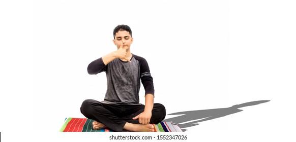 Full body shot of male teenager doing Nadi Shdhana Pranayama or Alternate Nostril Breathing isolated on white background. Male yoga pose. Horizontal shot.