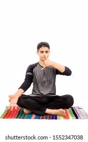 Full body shot of male teenager doing Nadi Shdhana Pranayama or Alternate Nostril Breathing isolated on white background. Male yoga pose. Vertical shot.