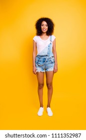 Full body shot of pretty charming girl in white t-shirt jeans jumpsuit with slim legs looking at camera isolated on yellow background