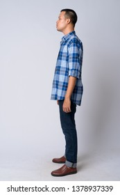 Full body shot profile view of young Asian hipster man