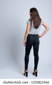Full body shot rear view of young beautiful multi-ethnic woman standing