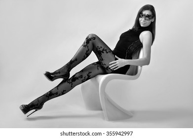 Full body shot of sexy brunette woman wearing back dress and mask on isolated white studio background with S-shape plastic chair