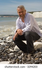 Full body shot of a smiling tanned fortyish handsome white male crouched down on a beach wearing a white shirt and dark trousers with the sea and white chalk cliffs of southern England behind him.