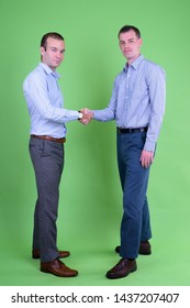 Full body shot of two businessmen shaking hands together