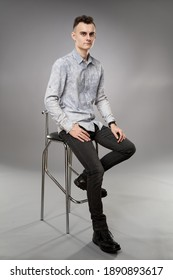 Full body shot of a young businessman sitting on a high chair