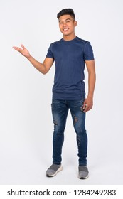 Full body shot of young happy Asian man showing something