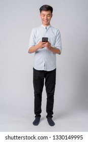 Full body shot of young happy Asian businessman using phone