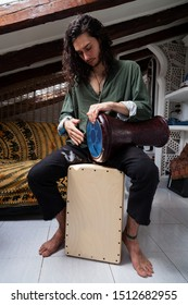 Full body shot of a young hippie handsome man playing cajon drum box and arabic darbuka at the same time on an alternative house studio background. Having fun experimenting with exotic instruments.