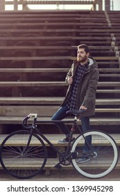 Full body shot of a young male holding his bicycle and smiling.Lifestyle concept shot.