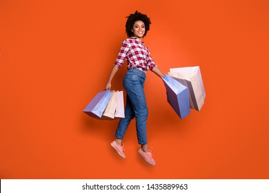 Full body side photo of jumping high wavy lady sale discount hold many packs wear jeans denim pants plaid shirt isolated orange bright background