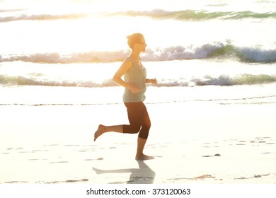 Full body side portrait of active young woman running on beach with bright sunlight