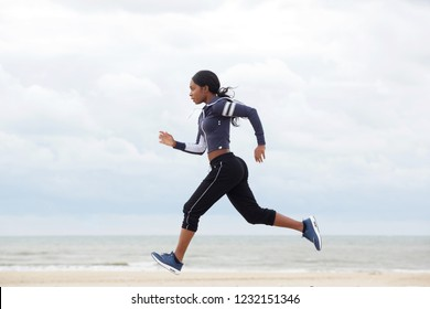 Full body side portrait of african american woman running by the beach