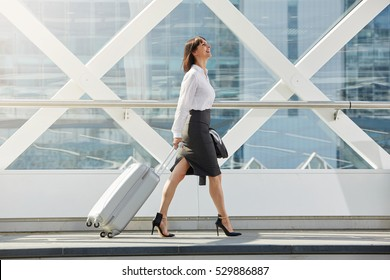 Full body side portrait of business woman walking with suitcase in terminal