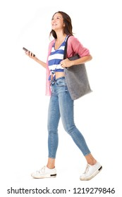 Full body side portrait of fashionable young asian woman walking with handbag and mobile phone against isolated white background