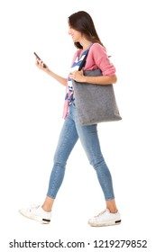 Full body side portrait of fashionable young asian woman walking with purse and mobile phone against isolated white background