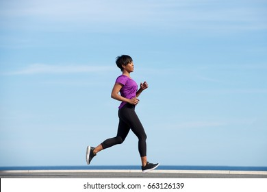 Full body side portrait of fit young african woman running outdoors against blue sky