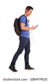 Full body side portrait of happy mature man holding cellphone with backpack and headphones on white background