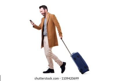 Full body side portrait of happy man walking with mobile phone and suitcase against isolated white background