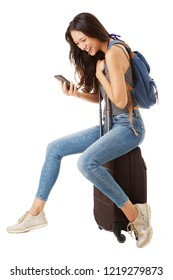 Full body side portrait of happy asian female traveler sitting on suitcase and looking at cellphone against isolated white background