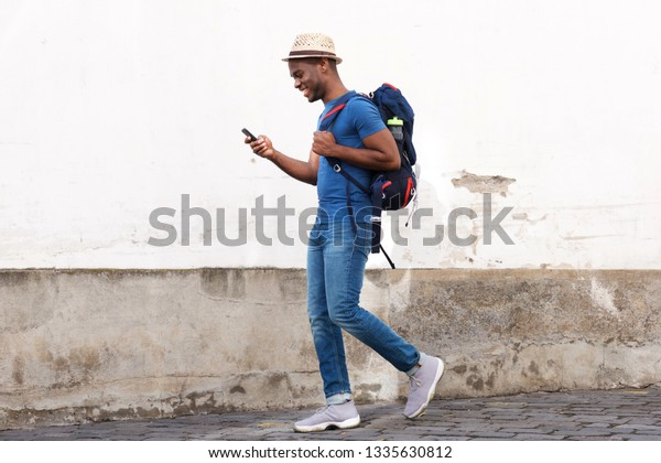 Full body side portrait of happy african american tourist man walking with bag and cellphone