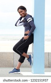 Full body side portrait of healthy young african american woman leaning against pole