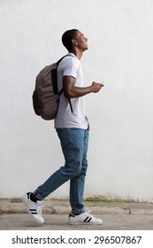 Full body side portrait of a smiling male college student walking with bag and mobile phone