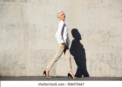 Full body side portrait of a smiling female fashion model walking
