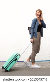 Full body side portrait of young travel woman walking and talking with mobile phone against white wall
