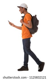 Full body side portrait of young african american man walking on isolated white background with cellphone and bag
