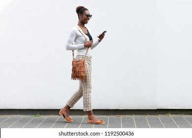 Full body side portrait young african american woman walking against white wall with cellphone