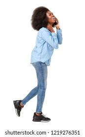 Full body side portrait of young black woman walking and talking on cellphone