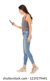 Full body side portrait of young asian woman looking at mobile phone against isolated white background