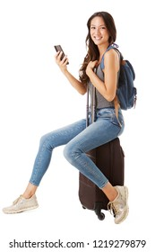 Full body side portrait of young female asian traveler sitting on suitcase and holding mobile phone against isolated white background