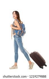 Full body side portrait of young asian woman walking against isolated white background with suitcase and bags