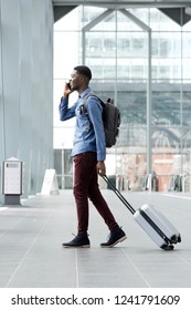 Full body side portrait of young african american man traveling with suitcase and cellphone at airport