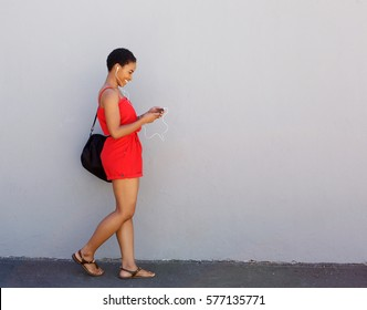 Full body side portrait of young smiling woman walking with mobile phone and earphones