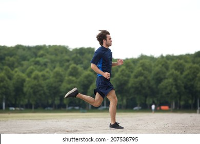 Full body side view of an athletic young man running outdoors