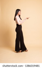 Full body side view of beautiful young asian woman pointing on  beige background