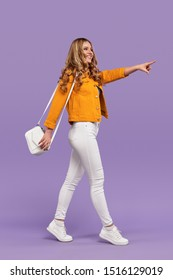 Full body side view of cheerful young female in trendy casual outfit smiling and pointing at distance while walking against purple background