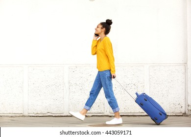 Full body side view portrait of young woman traveling with suitcase and talking on mobile phone