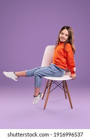 Full body side view of smiling little girl in orange sweatshirt and jeans with white sneakers sitting on chair in studio against violet background - Shutterstock ID 1916996537